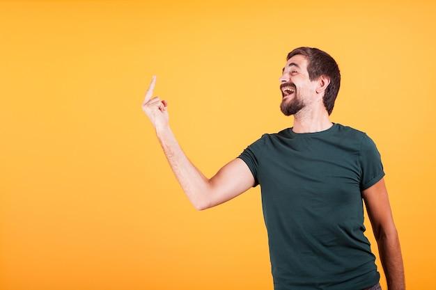 Man die zijn middelvinger toont aan iemand uit het frame met beschikbare copyspace. geïsoleerd op gele achtergrond