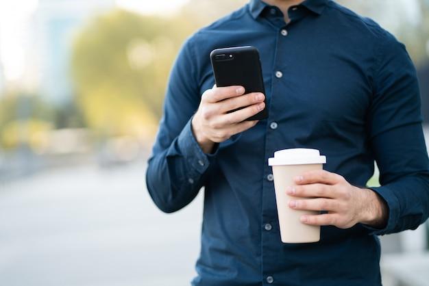 Man die zijn mobiele telefoon gebruikt en een kopje koffie vasthoudt terwijl hij buiten op straat staat