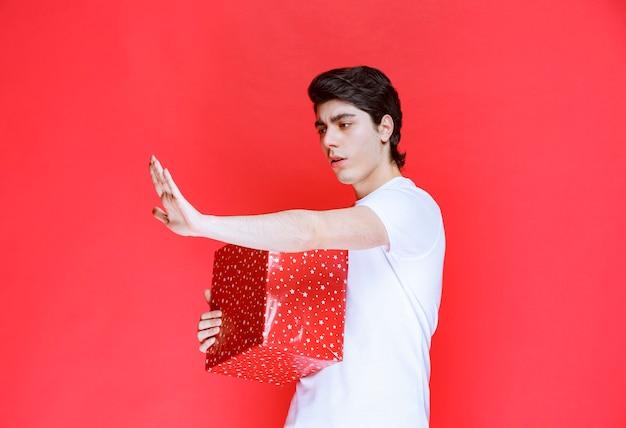 Man die zijn rode geschenkdoos stevig vasthoudt en mensen tegenhoudt