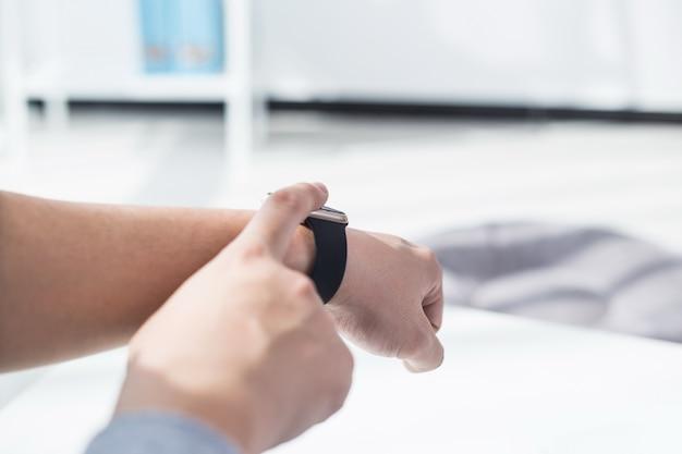 Man die zijn smart watch app gebruikt close-up handen
