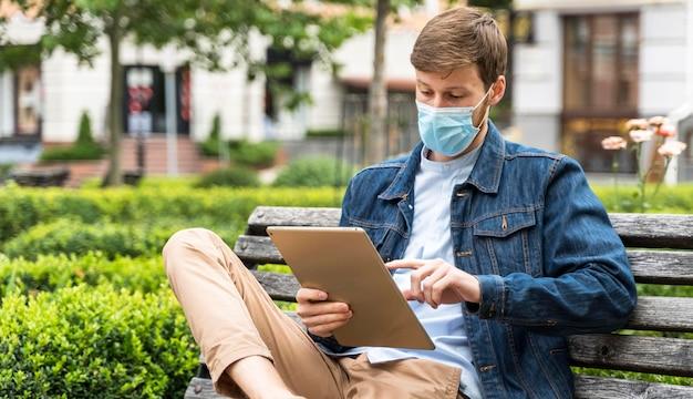 Man die zijn tablet controleert terwijl hij een medisch masker draagt
