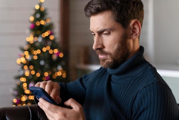Man die zijn telefoon controleert op eerste kerstdag