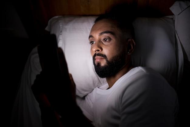 Man die zijn telefoon controleert voordat hij gaat slapen