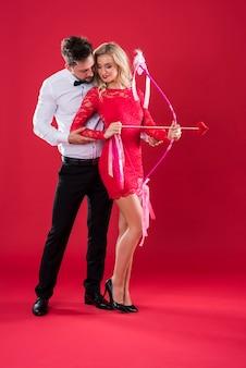 Man die zijn vrouw leert hoe ze een cupido-boog moet gebruiken