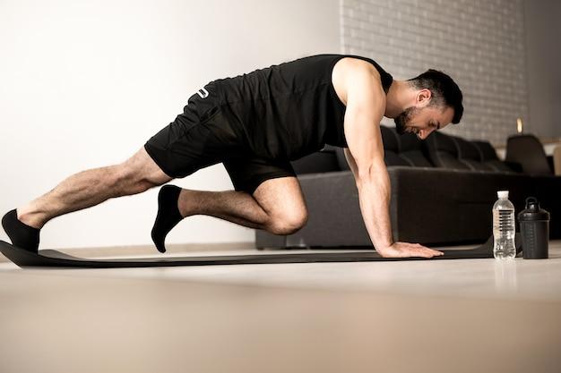 Man doet bergbeklimmer oefeningen op zwarte yoga mat. ochtend training. witte moderne woonkamer op achtergrond. plastic fles water. moeilijke oefening. thuis trainen.