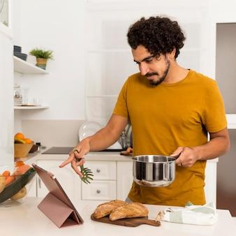 Man doet een recept terwijl hij het van internet leert