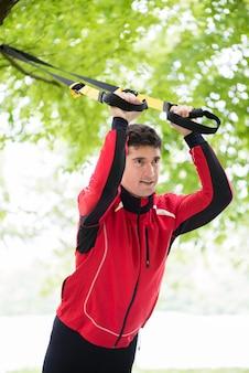Man doet fitness slinger training buitenshuis