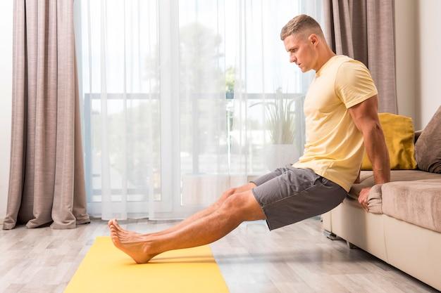 Man doet fitness thuis met behulp van de bank