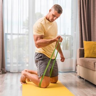 Man doet fitness thuis met behulp van elastische band