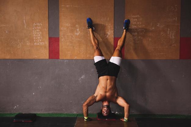 Man doet handstand in de sportschool