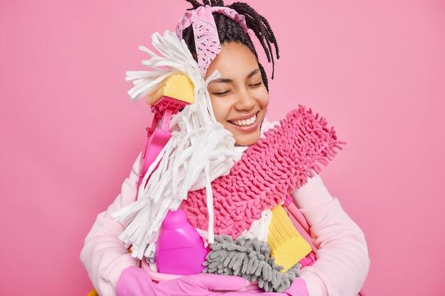 Man doet huishoudelijke klusjes omarmt schoonmaakgereedschap en wasbak geniet van huishoudelijk werk glimlacht graag geïsoleerd op roze