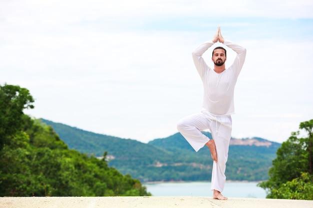Man doet indiase klassieke kunst yoga bij de zee en de bergen