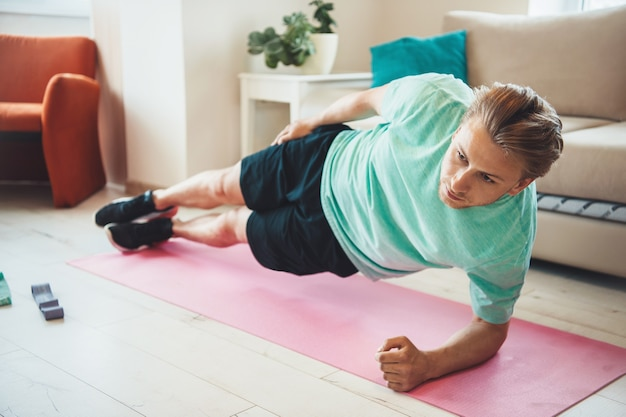 Man doet kant plank thuis tijdens het beoefenen van fitness tijdens de lockdown