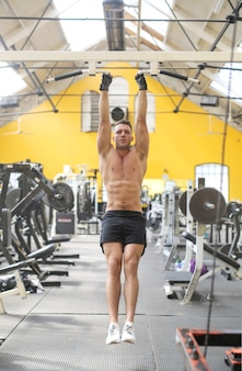 Man doet pull ups in de sportschool
