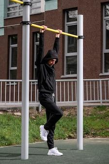 Man doet pull-ups op de horizontale balk tijdens het trainen 's avonds buitenshuis sterke atleet in trainingspak doen oefening op straatgymnastiekapparatuur