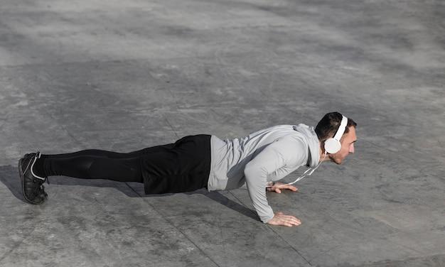 Man doet push ups en muziek luisteren