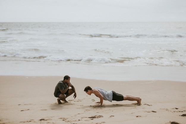 Man doet push-ups met een trainer op het strand
