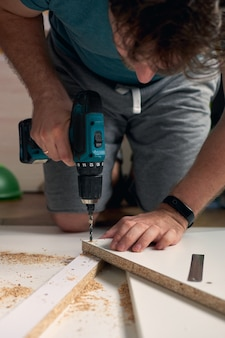 Man doet renovatiewerkzaamheden thuis boren met een schroevendraaier