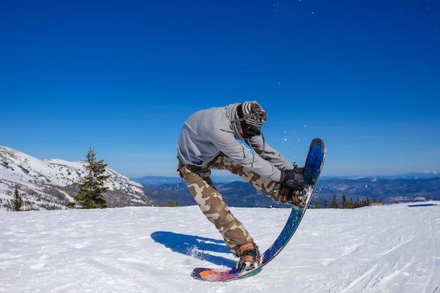 Man doet snowboarden springen op de achtergrond van de bergen