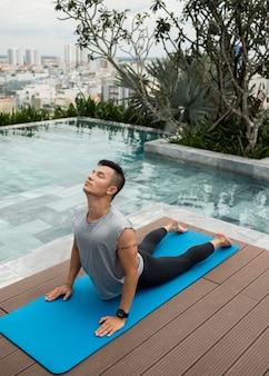 Man doet yoga bij het zwembad