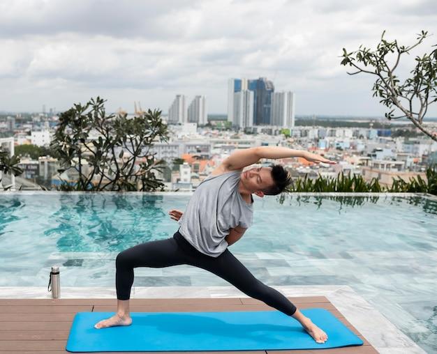 Man doet yoga buiten bij het zwembad