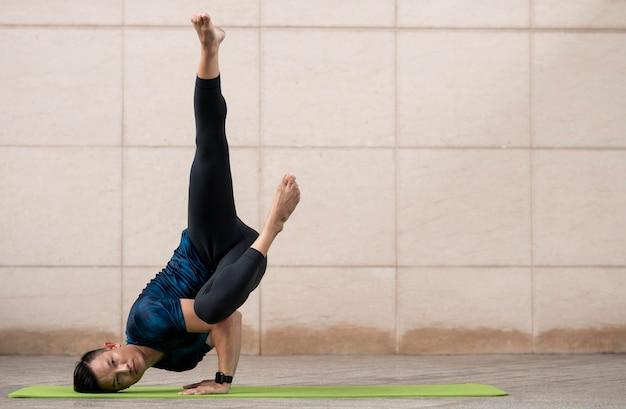 Man doet yoga buiten op mat met kopie ruimte