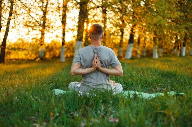 Man doet yoga in het park op een prachtige zonsondergang. gezonde levensstijl