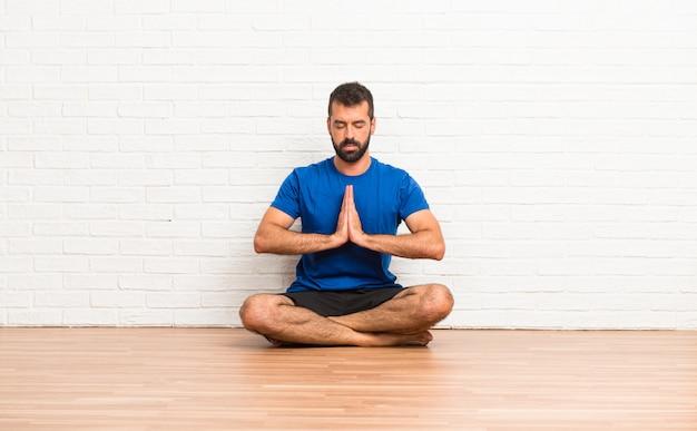 Man doet yoga oefeningen binnenshuis