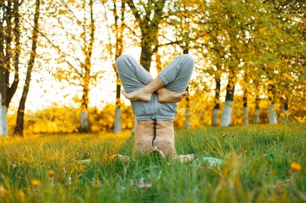 Man doet yoga op de natuur bij zonsondergang. gezonde levensstijl