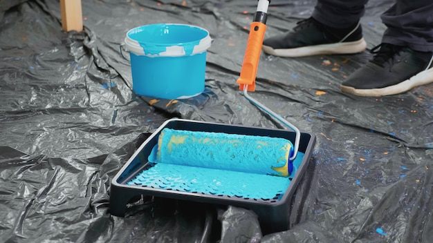 Man dompelen rolborstel in verf voor appartement decoratie. appartement herinrichting en woningbouw tijdens renovatie en verbetering. reparatie en decoreren.