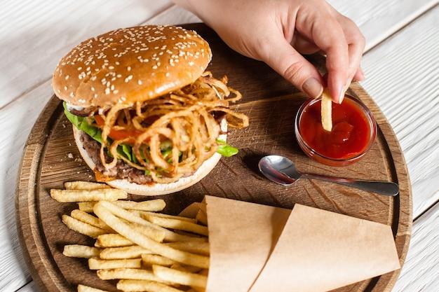 Man dompelt frietjes onder in rode saus bovenaanzicht