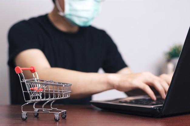 Man draag een masker om te beschermen tegen het corona-virus thuiswerkend op kantoor, online marketing, startende kmo, freelance man-concept.