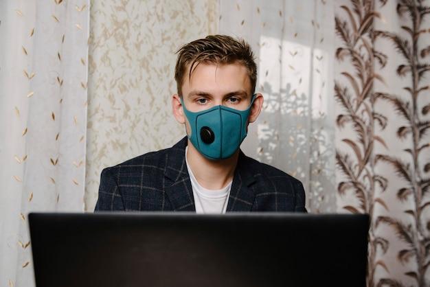 Man draag medisch masker werken met laptop. vermijd contact met andere mensen. blijf thuis. werken vanuit huis.