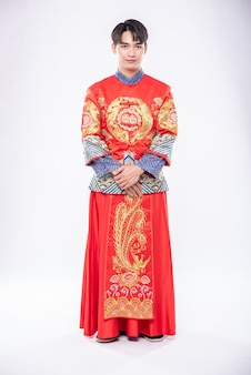 Man draagt cheongsam-glimlach om reizigers te verwelkomen die in chinees nieuwjaar winkelen