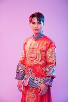 Man draagt cheongsam om reizigers te verwelkomen die winkelen in chinees nieuwjaar
