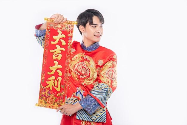 Man draagt cheongsam-pak geeft familie de chinese wenskaart voor geluk in chinees nieuwjaar