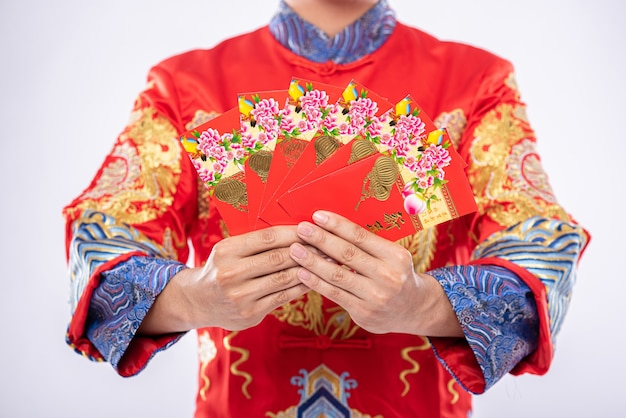 Man draagt cheongsam-pak geeft zijn familie een geschenk om een geluksvogel te zijn in het chinese nieuwjaar