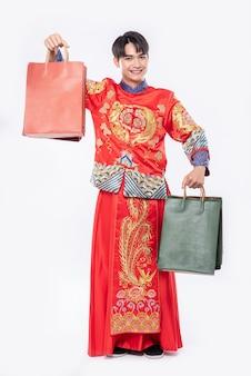 Man draagt cheongsam pak glimlach met papieren zak van winkelen in chinees nieuwjaar