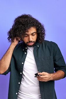 Man draagt draadloze hoofdtelefoons, gekrulde man in vrijetijdskleding geniet van muziek, moderne technologieën