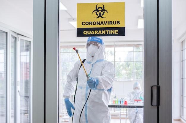 Man draagt een beschermend pak dat desinfectie en ontsmetting op quarantainekamer maakt