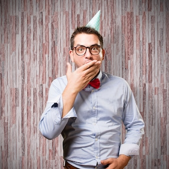 Man draagt een rode vlinderdas en feestmuts. op zoek verrast.