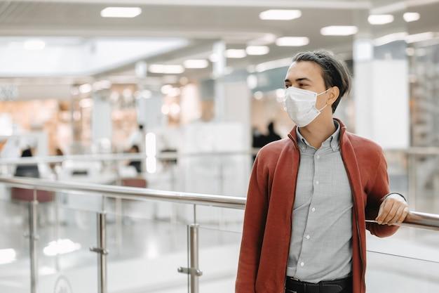 Man draagt medische masker tegen coronavirus terwijl boodschappen in de supermarkt