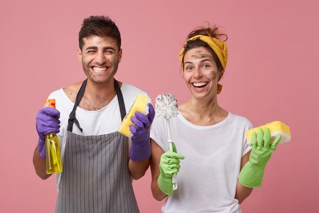 Man draagt schort en vrouw in wit t-shirt glimlachend in het algemeen blij om schoon te maken