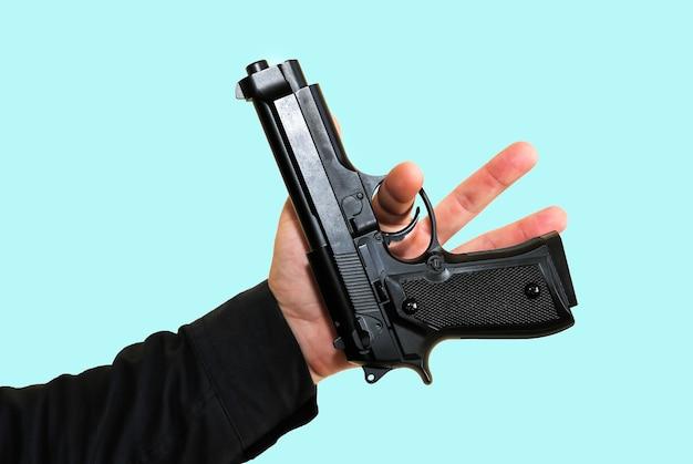 Man draait pistool op blauwe achtergrond. criminele moordenaar concept.