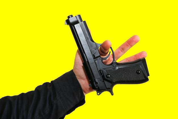 Man draait pistool op gele achtergrond. criminele moordenaar concept.