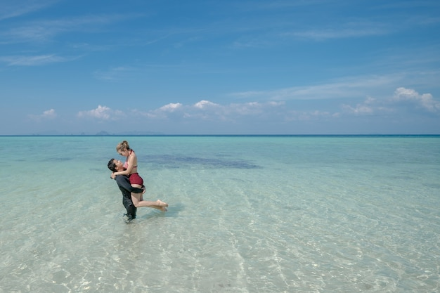 Man dragende bikini vrouw op zeewater door wit zandstrand. blauwe zee en lucht landschap. zomervakantie.