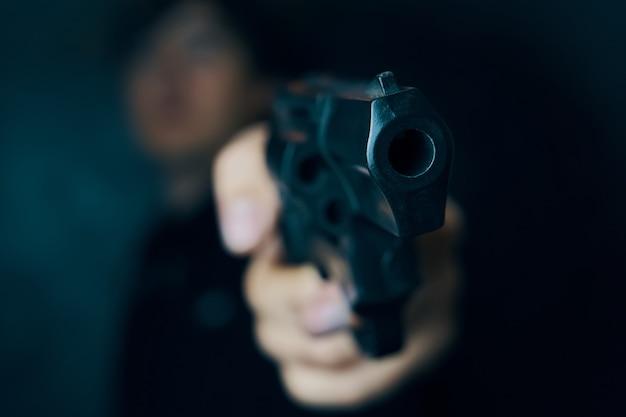 Man dreigt met vuurwapenrevolver in handen van man crimineel met een wapenmoordenaar of gewapende dief