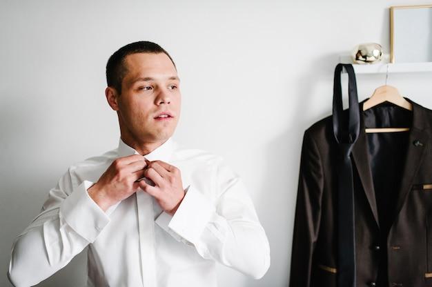 Man dressing shirt thuis. man bevestigende knopen op zijn overhemd. kleding concept.