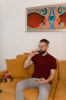 Man drinken van wijn zittend op de bank thuis