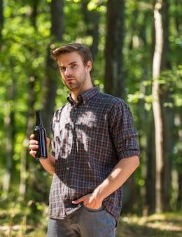 Man drinkt bier in bos. ontspannen op zomer picknick weekend. kampeerseizoen begint. hij houdt van wandelen. toerisme avontuur concept. bier drinken op de camping. laat geen afval achter in het bos. ecologische vervuiling.